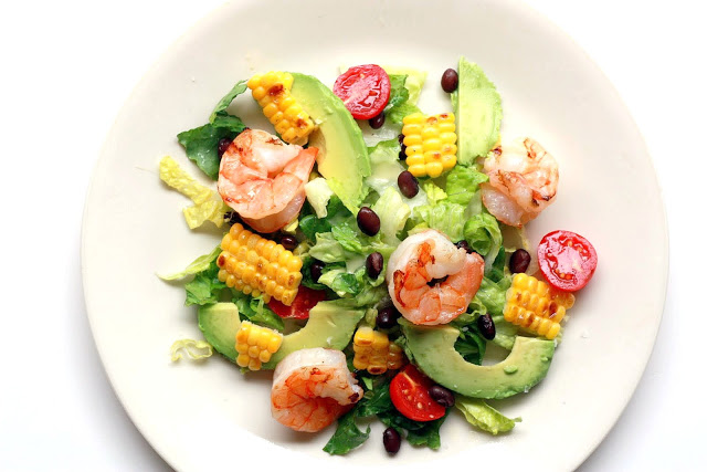 A healthy salad with grilled corn, shrimp, avocado, black beans, and tomato.