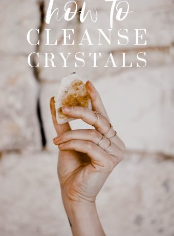 """A hand holds up a yellow crystal. White text overlay reads, """"how to cleanse crystals"""""""