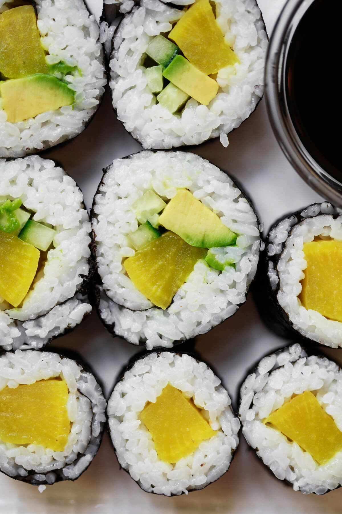 An overhead close-up photo of oshinko rolls with avocado and cucumber. A delicious veggie sushi recipe.