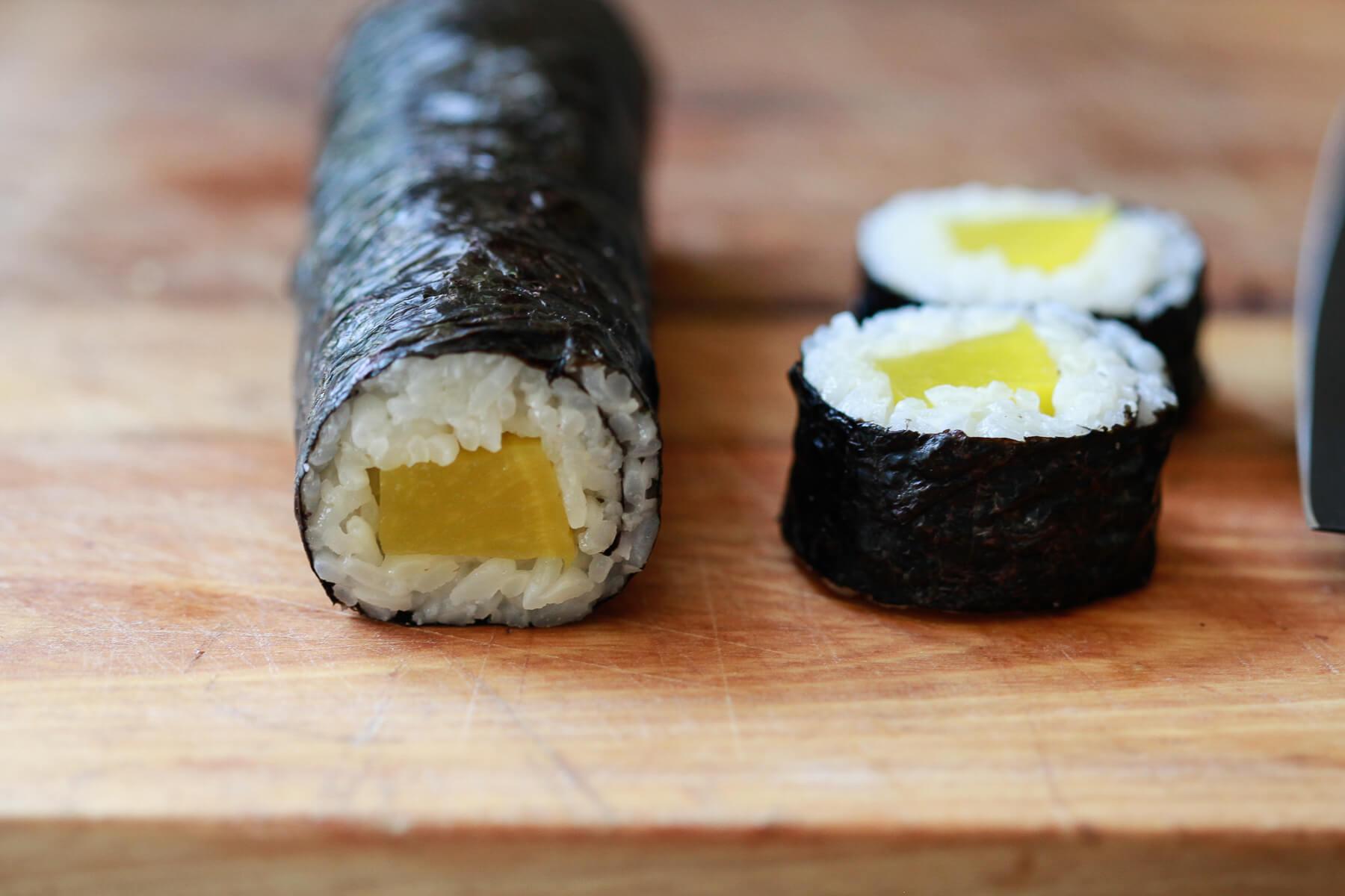 Cutting an oshinko sushi roll into slices.