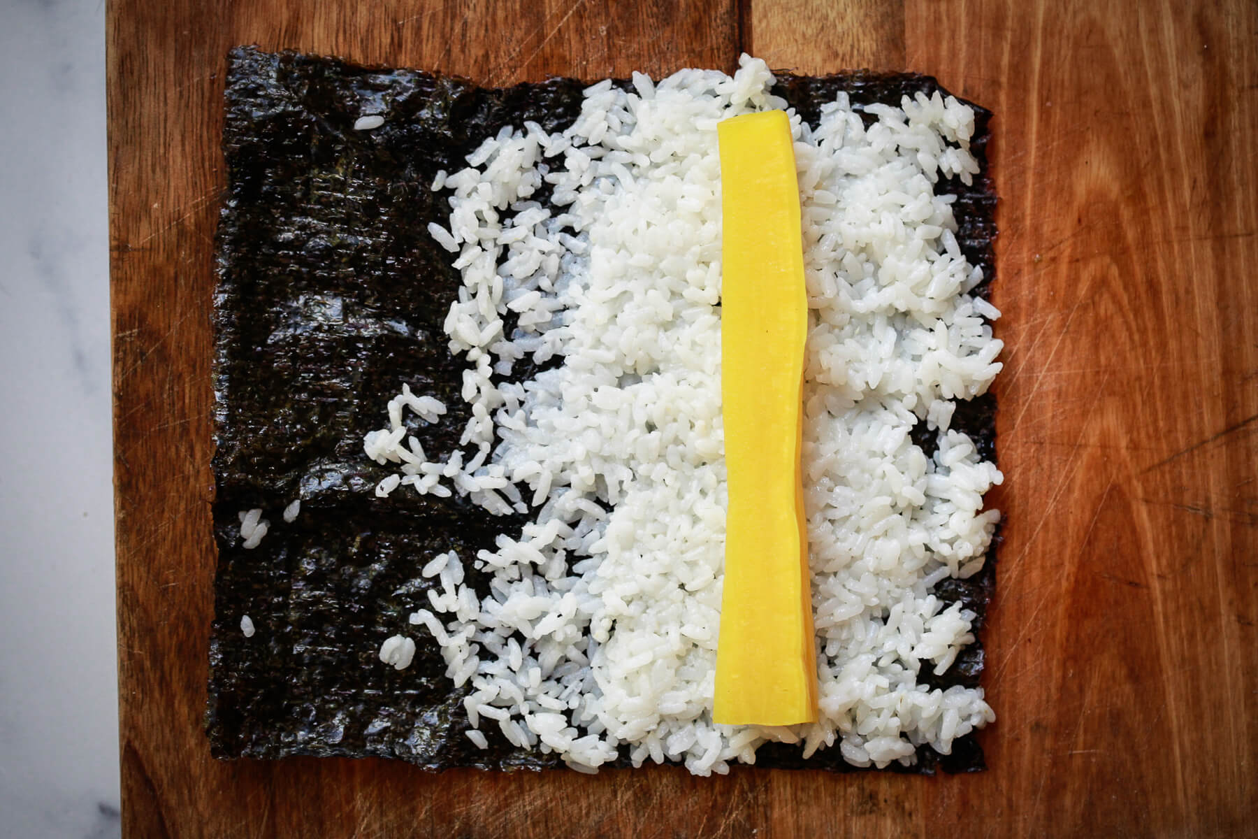 Nori is partially covered with sushi rice and a piece of oshinko is on top.