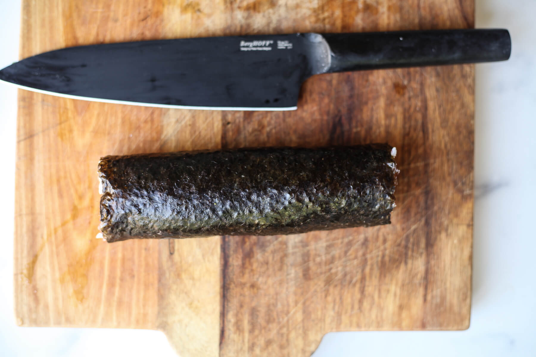 A rolled sushi sits on a cutting board next to a knife before slicing.