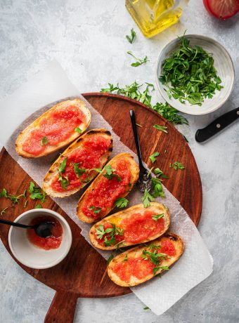 A beautiful overhead photo of 5 pieces of pan con tomate on a wood cutting board on a light grey background.