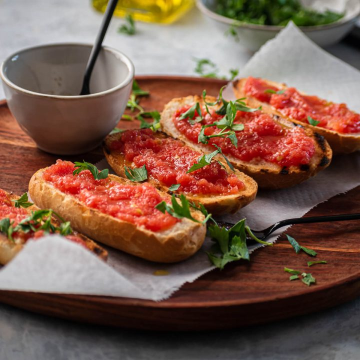 Pan con tomate on a wood cutting board garnished with parsley.