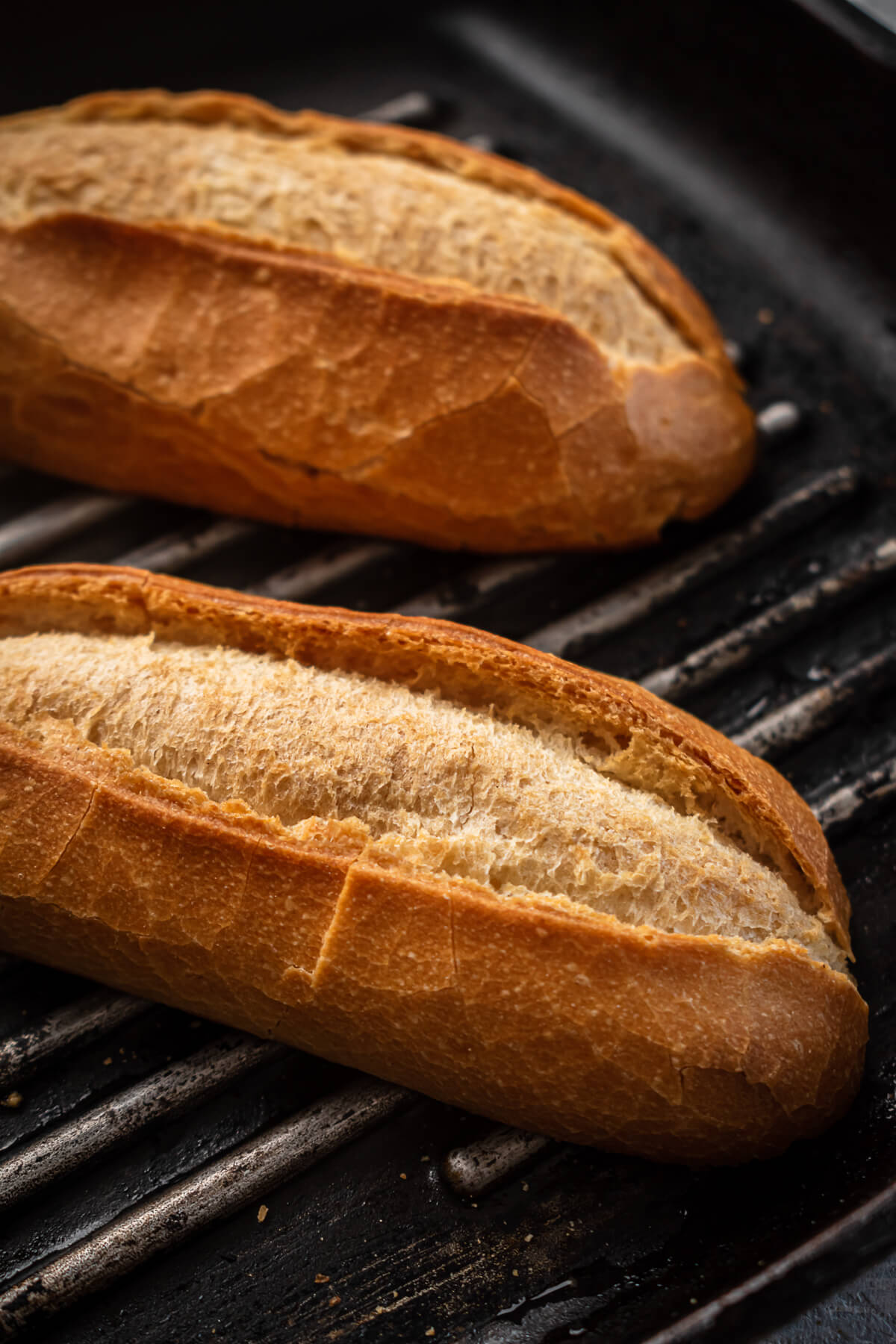 Baguette halves toast on a grill.