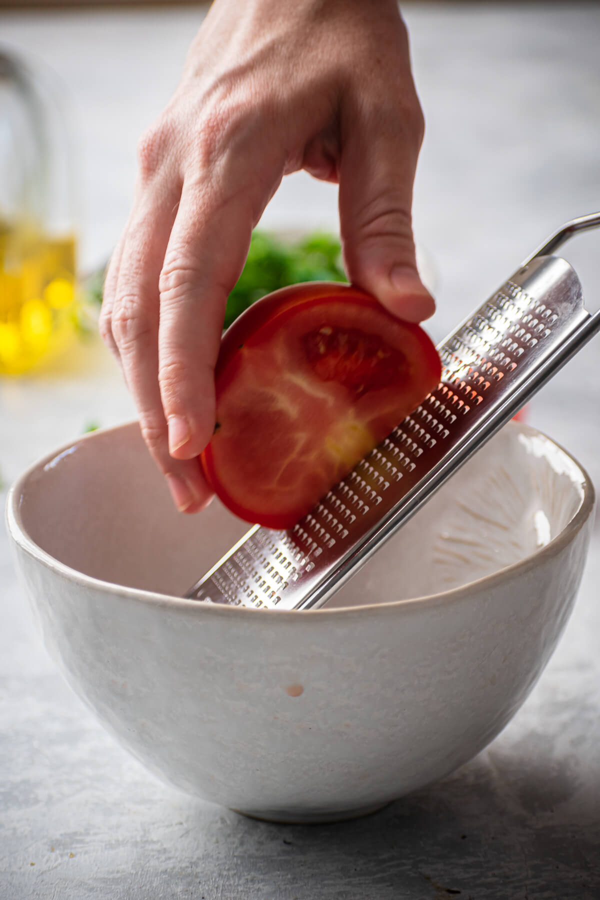 A tomato is grated into a bowl.