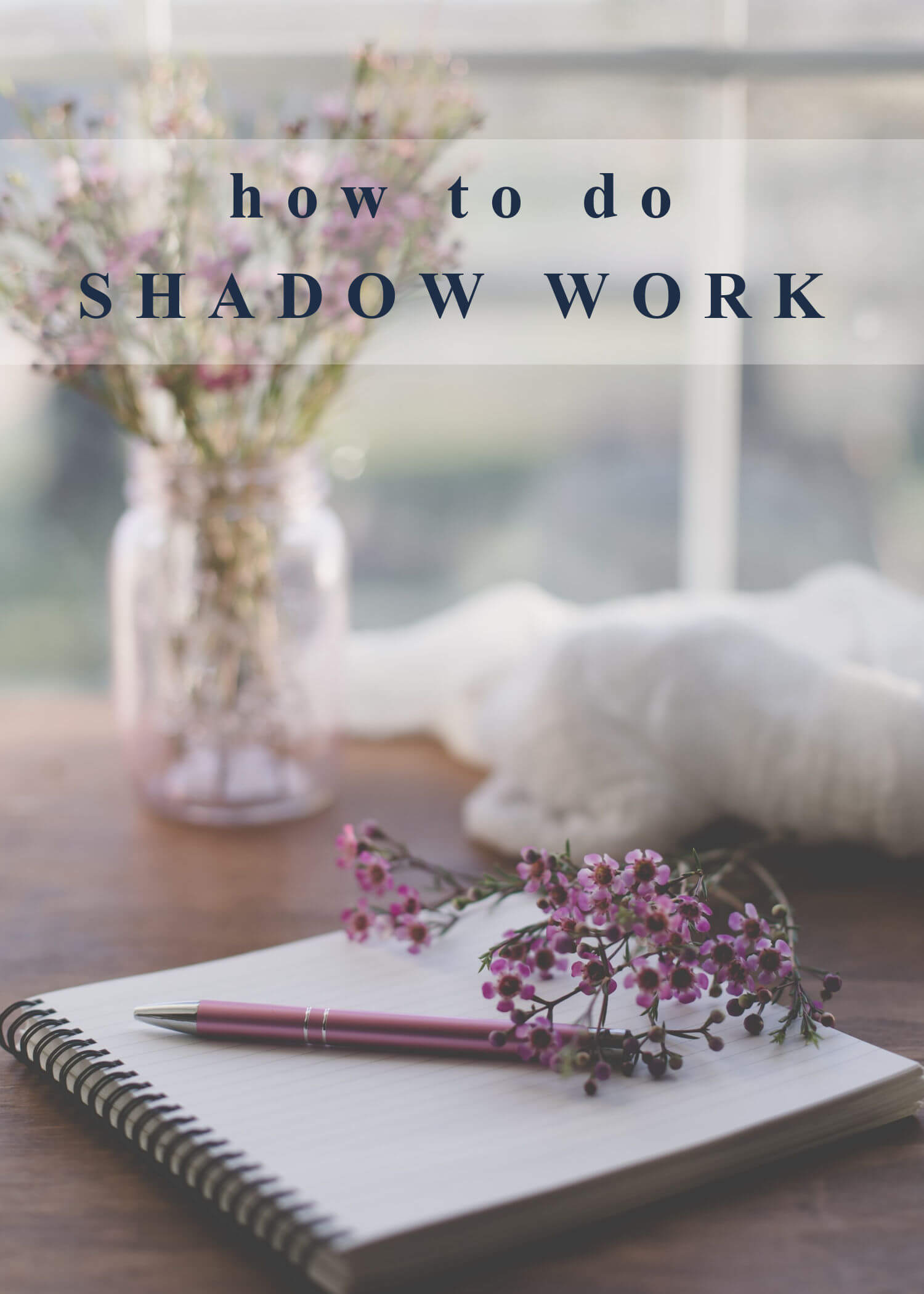 """A beautiful photo of a journal with a pen on a wooden desk with a jar of purple flowers in the background. Text overlay reads, """"how to do shadow work."""""""