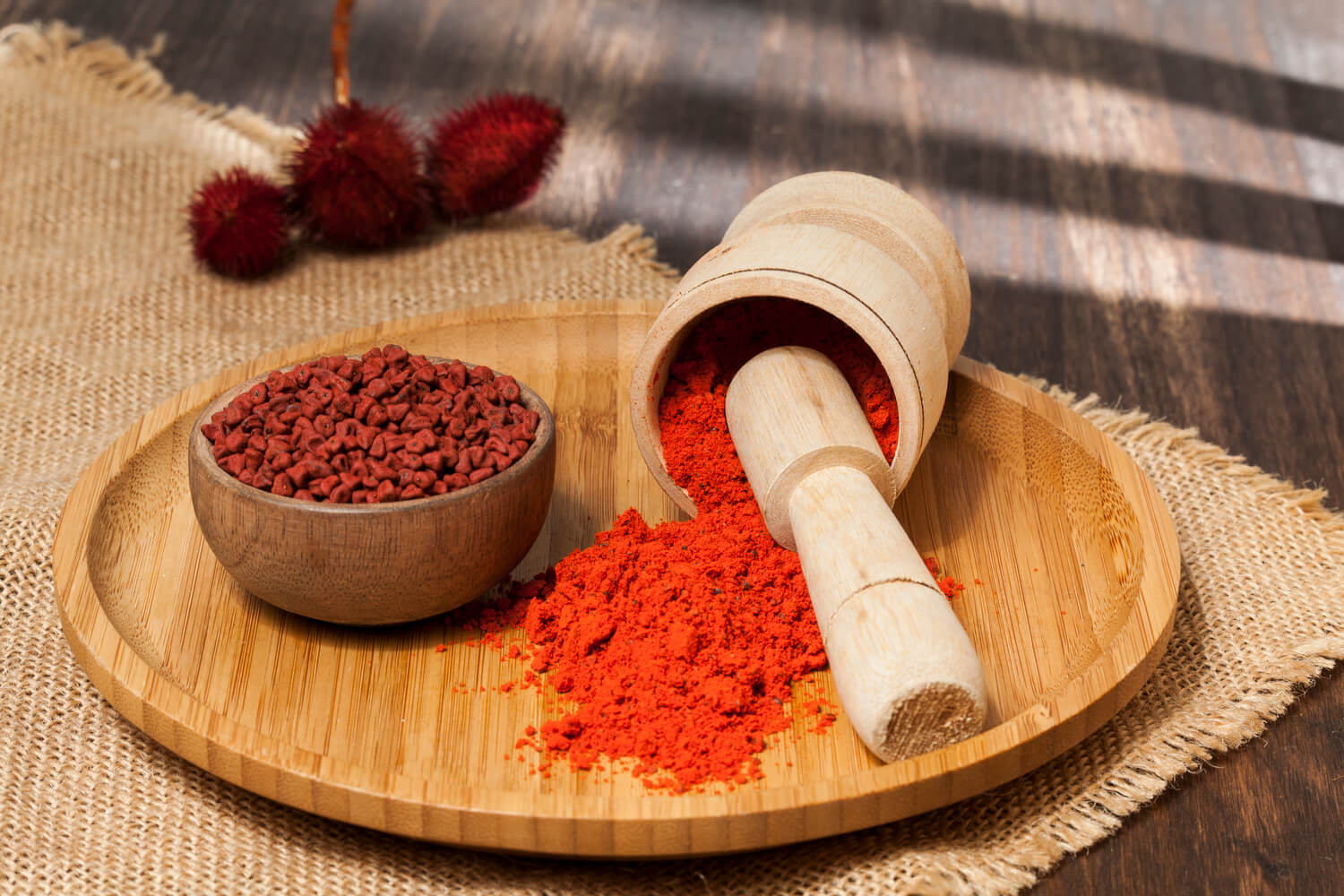 A bowl of achiote seeds sits next to a mortar and pestle filled with ground annatto.