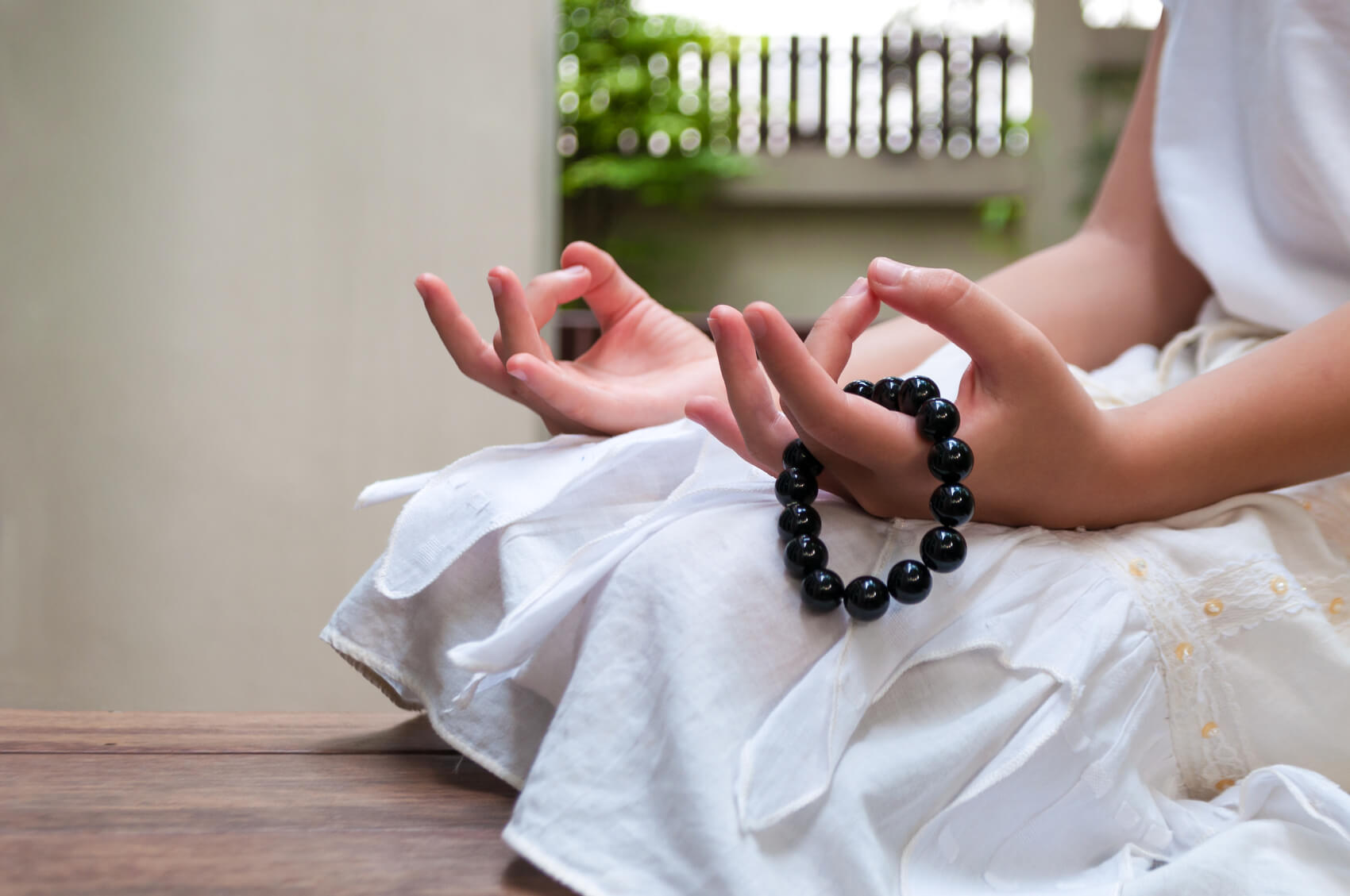 Meditating hands hold a black obsidian bracelet for anxiety.