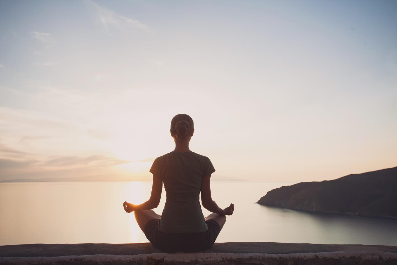 A woman sits facing away toward the ocean at sunset meditating.
