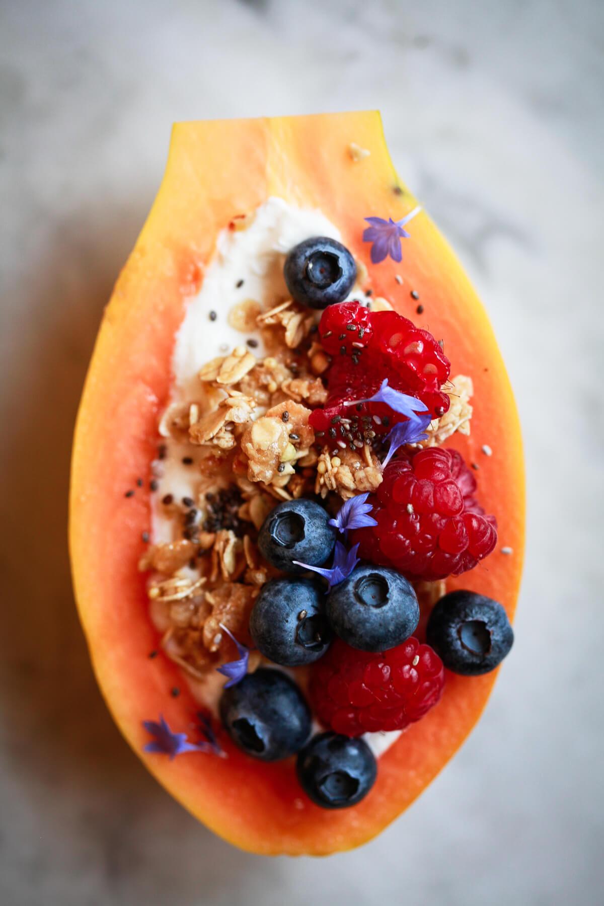 An overhead photo of half a Hawaiian papaya filled with plain yogurt, granola, fresh berries, and chia seeds.