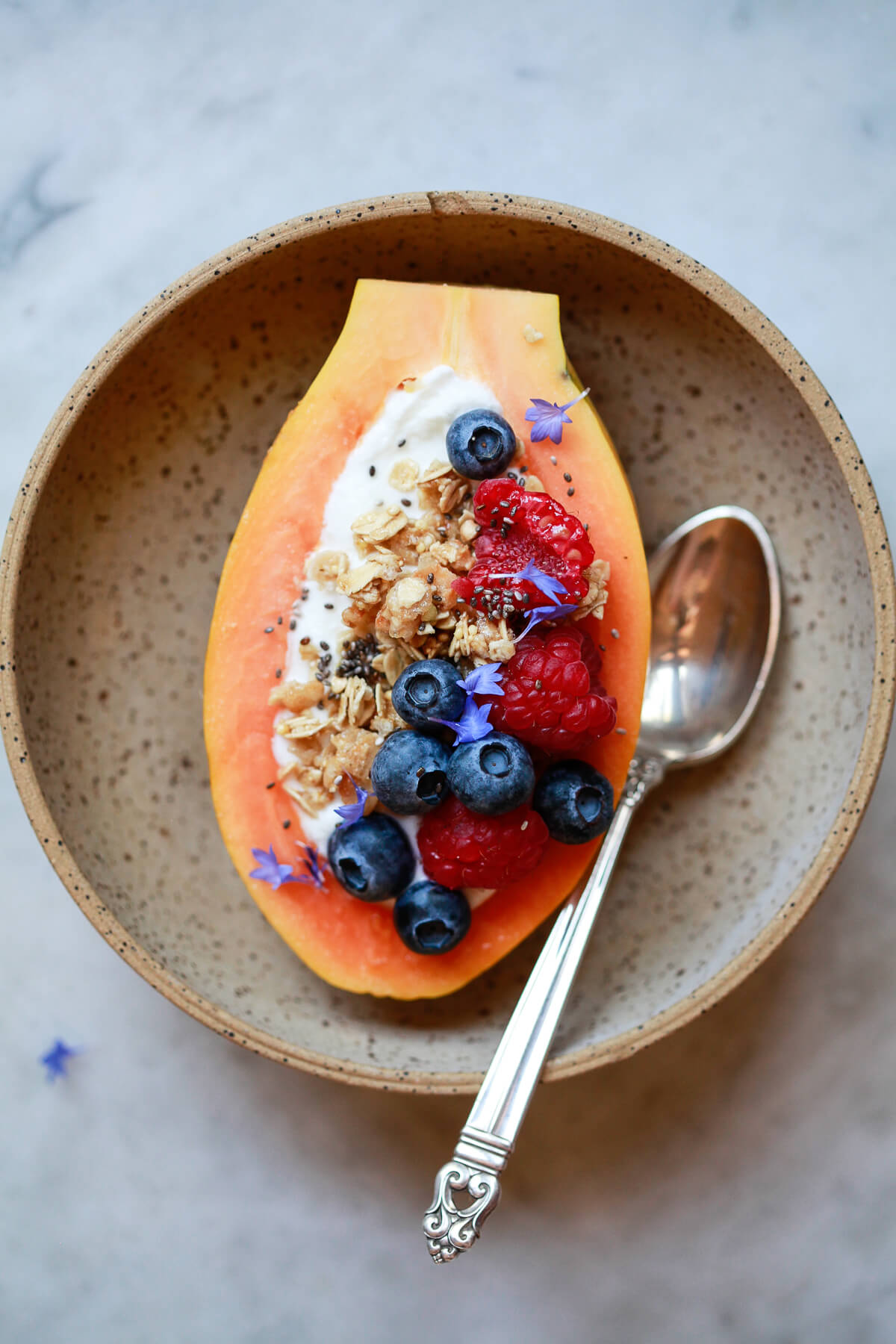A papaya boat filled with yogurt, granola, and berries in a stone bowl with a silver spoon.