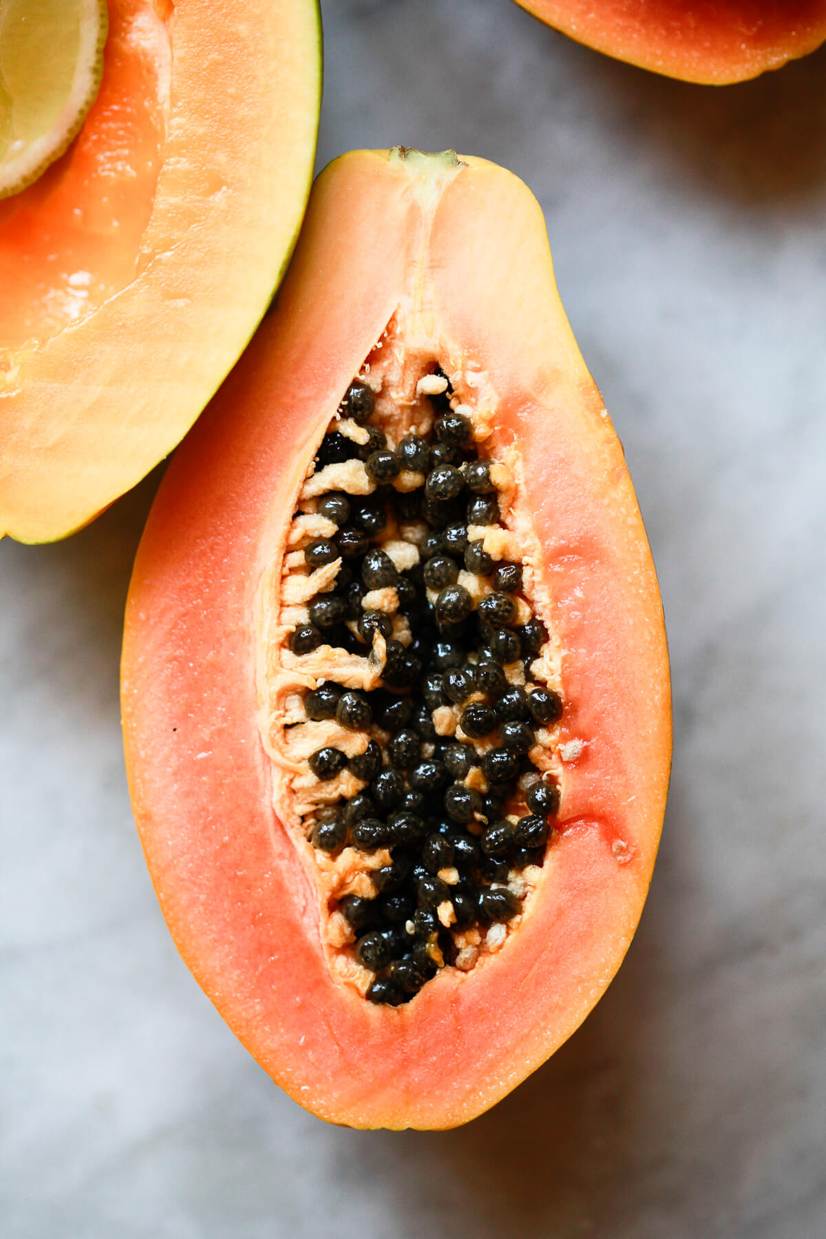 Half a papaya with seeds sits on a marble countertop.