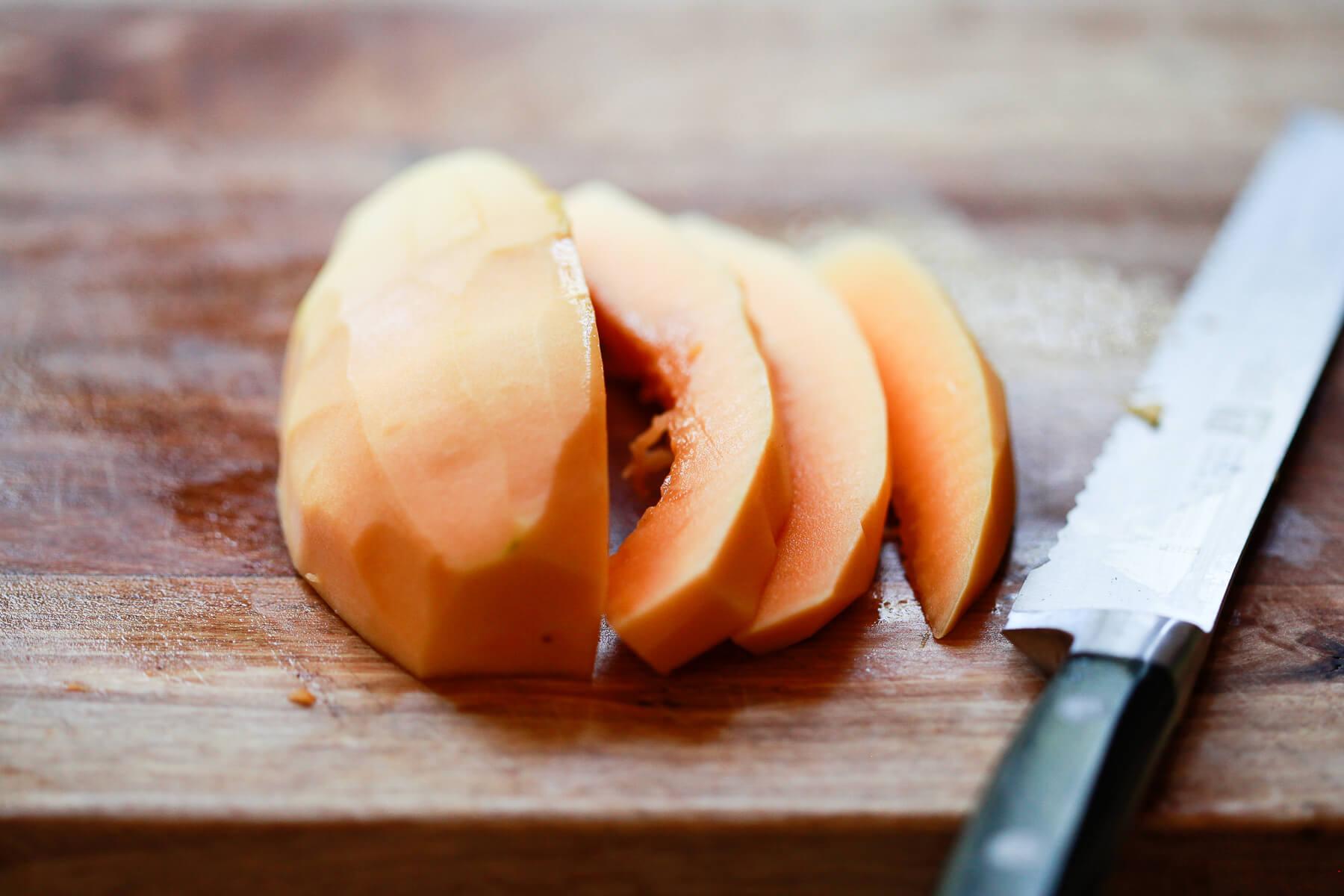 Hawaiian papaya has been peeled and cut into slices on a cutting board.