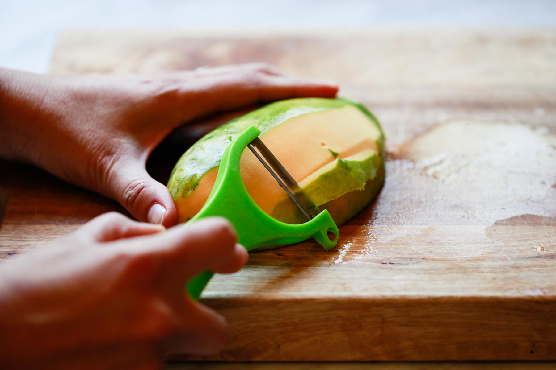 A green vegetable peeler is used to peel a papaya.