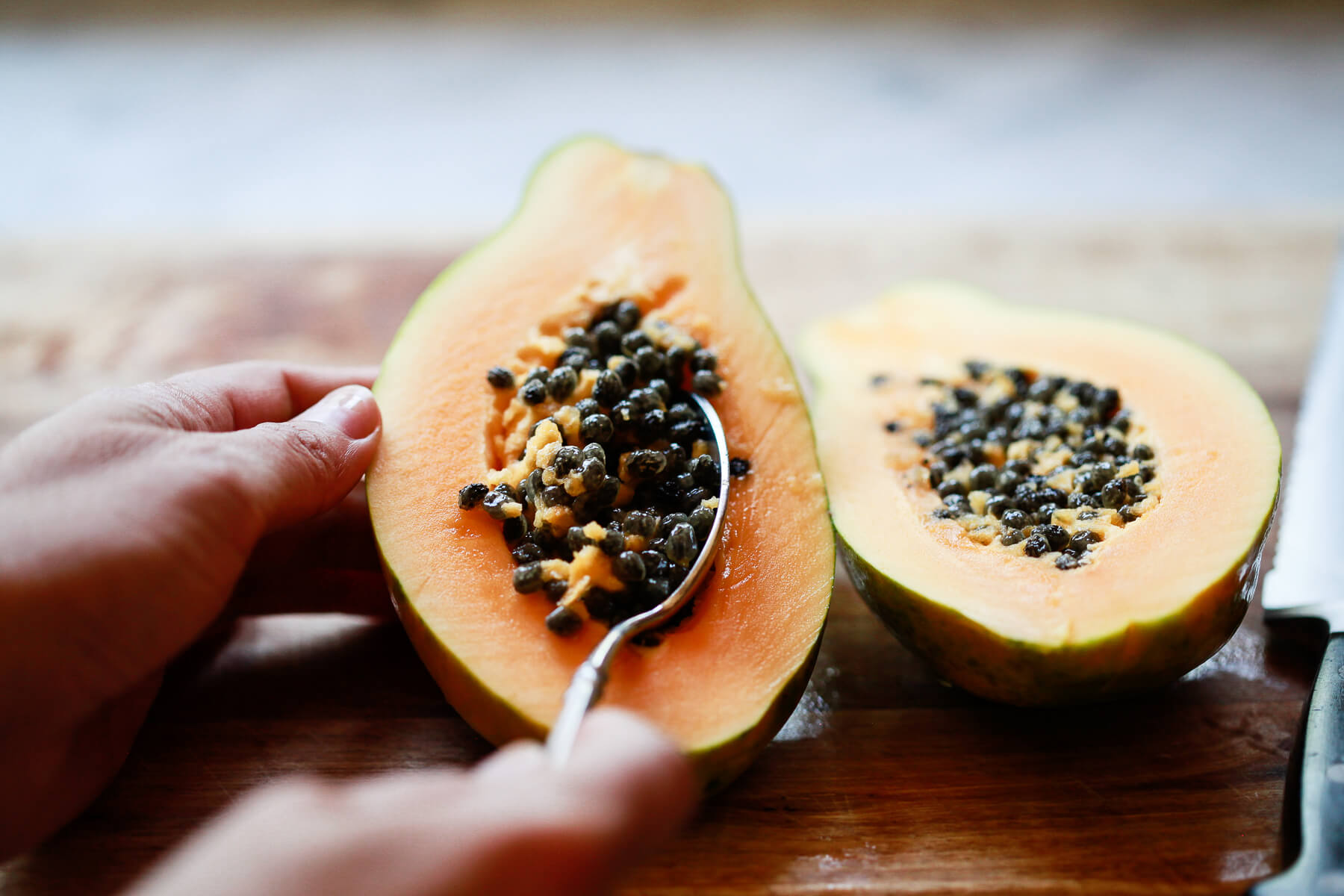 A spoon scoops the seeds out of a Hawaiian papaya.