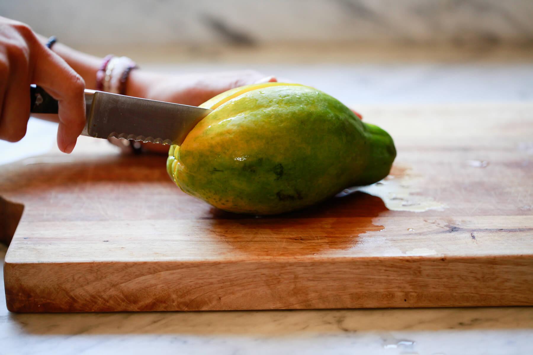 A knife cuts a papaya in half.