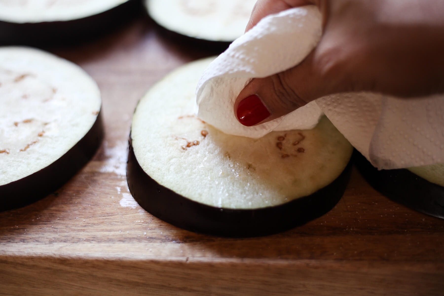 Water and salt is wiped off of a salted eggplant round with a paper towel.