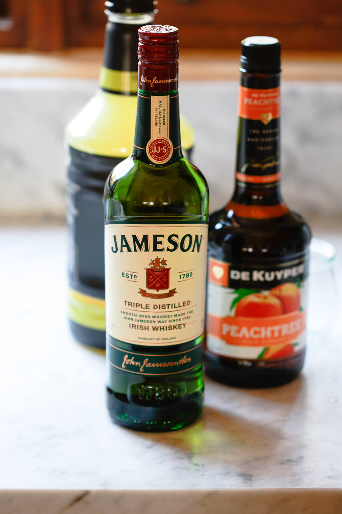 Three alcohol bottles sit on a marble countertop: Jameson Irish Whiskey in the foreground and peach schnapps and sweet and sour in the background.