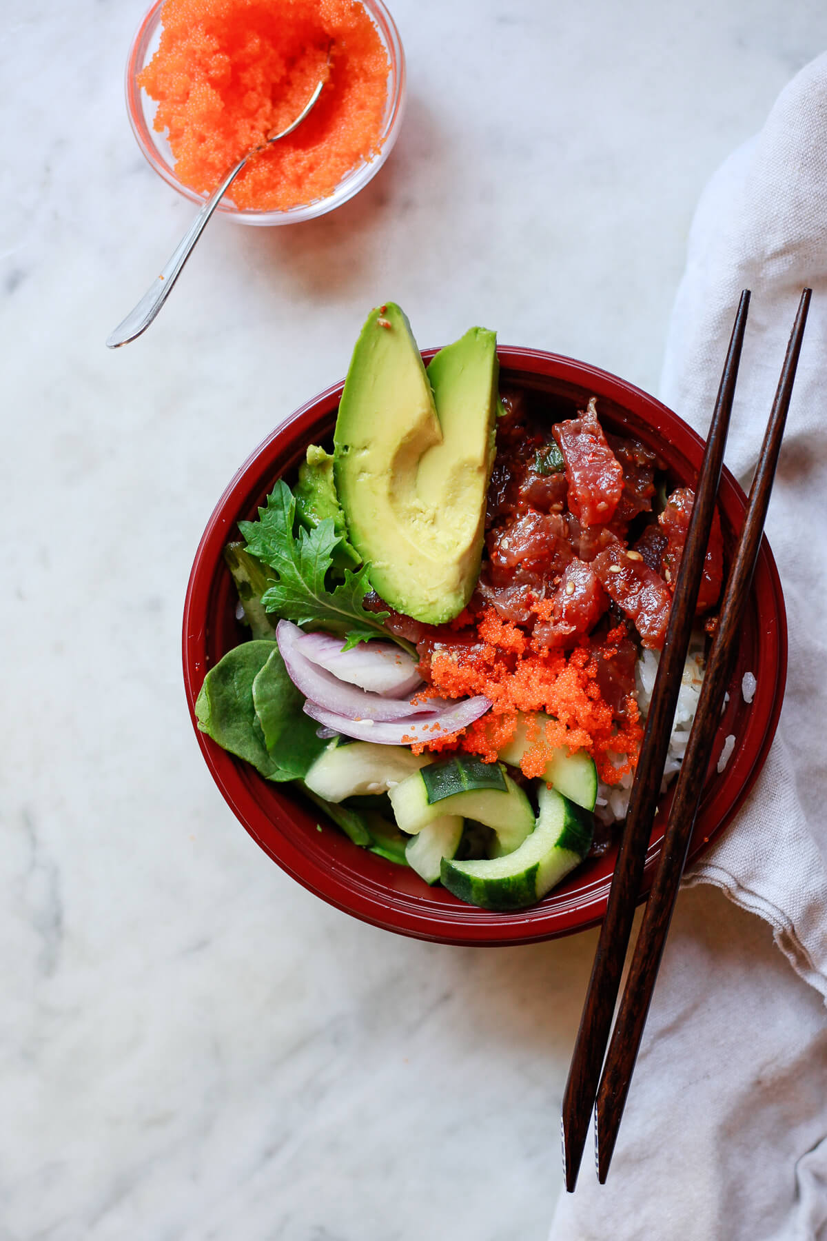 A spicy ahi poke bowl with avocado, greens, cucumber, onions, rice, and masago.