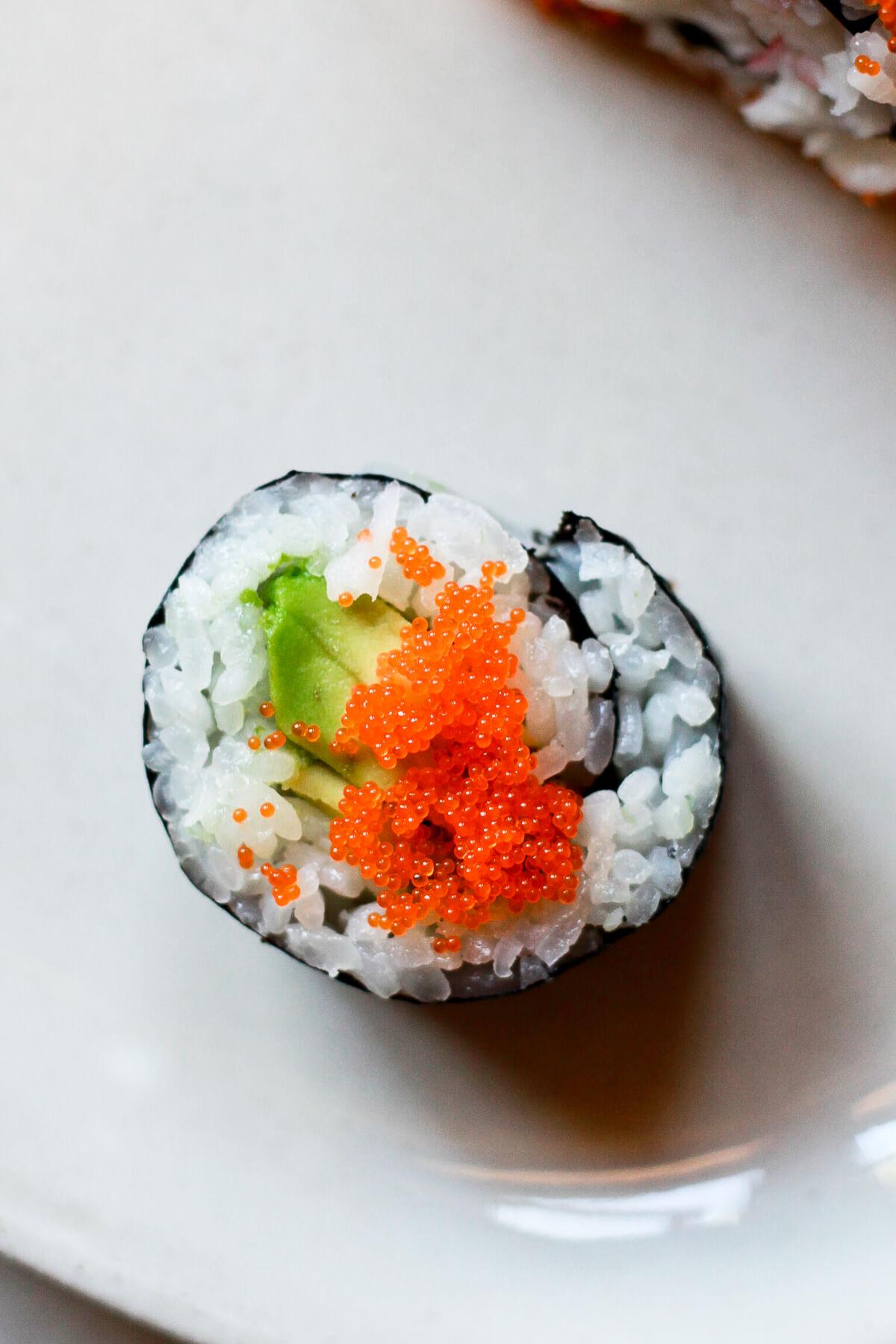 An overhead photo of a piece of avocado sushi with masago.