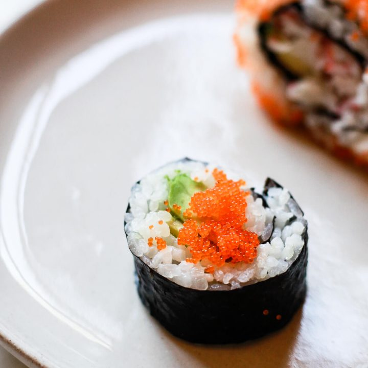 Two sushi rolls topped with masago.