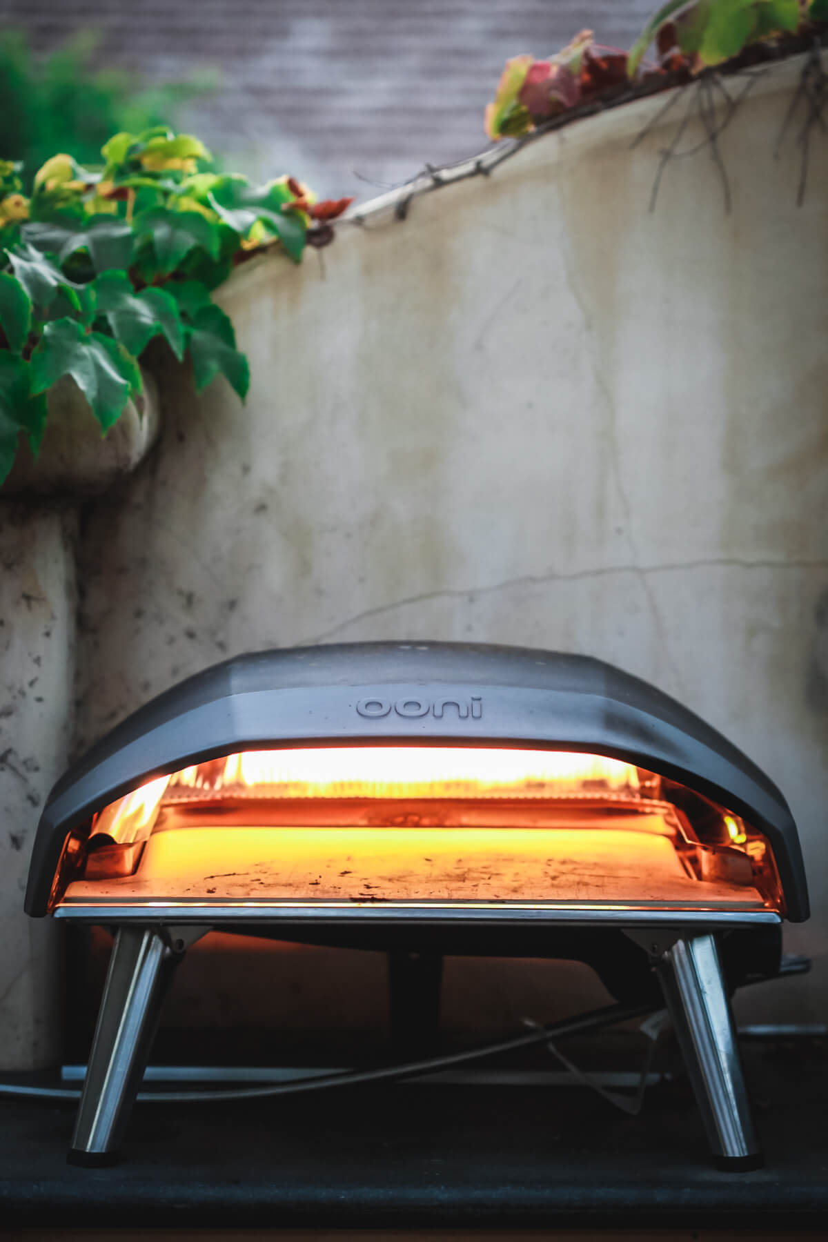 An Ooni Koda 16 pizza oven sits on an outdoor kitchen counter.