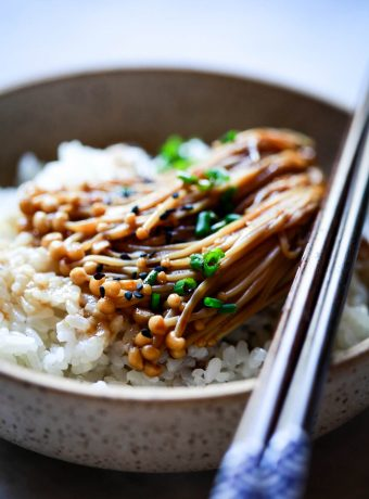 Enoki mushrooms with teriyaki and soy sauce served over rice and topped with chives and black sesame seeds.