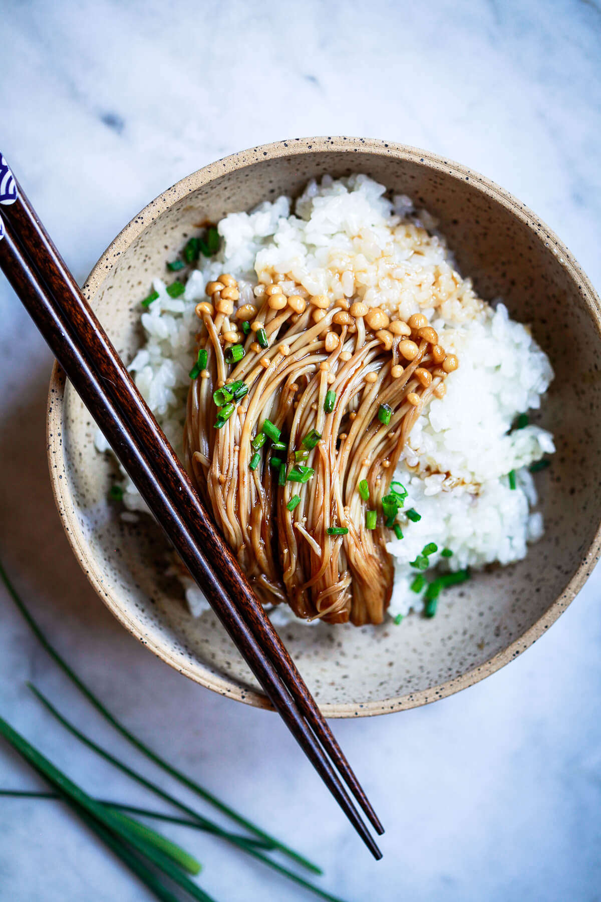 An overhead photo of Enoki mushroom with teriyaki sauce over a bed of rice and topped with black sesame seeds and chives.