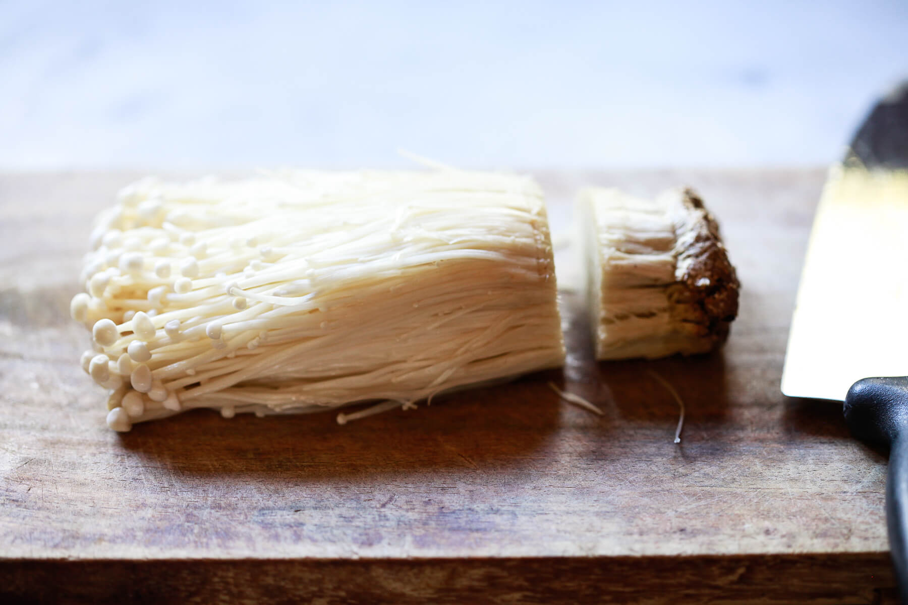 Enoki mushrooms with the root cut off.
