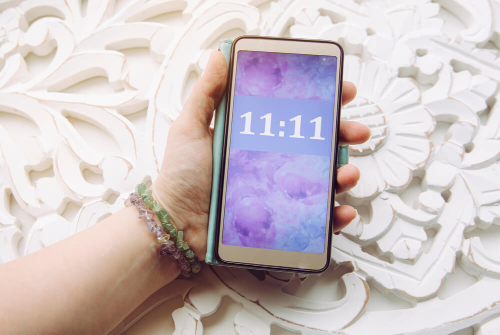 A hand holds a phone with 11:11 on the screen to show an angel number.
