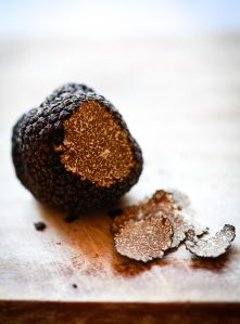 A fresh black truffle sits on a wooden cutting board. A few thin pieces have been shaved off to reveal a marbled interior.
