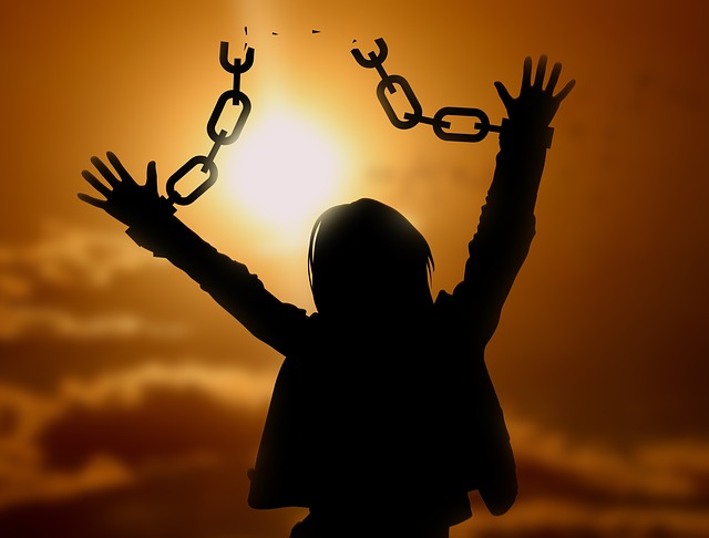 woman breaking free of chains holding her back