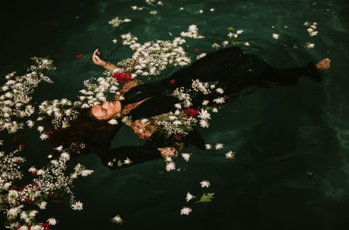 Woman back floating in water with flowers.