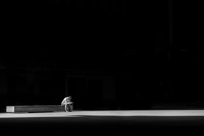 Man alone in the dark on a bench