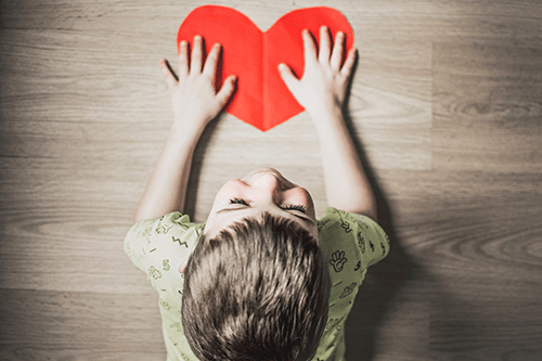 Little boy with his hands touching a paper cut out of a red heart.