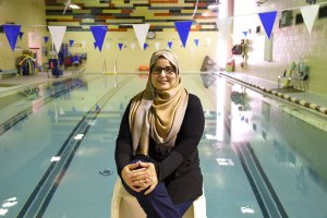 Faiza Elbarghathi is smiling to the camera in front of YWCA Hamilton swimming pool