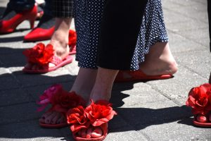 A closeup of two feet in red floral flip flops.