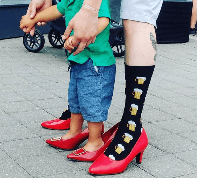 A man in red high heels holds hands with a little boy also wearing red high heels