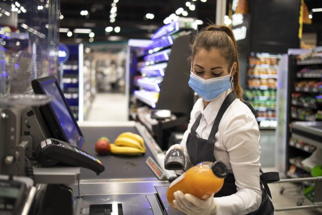 Cashier in supermarket wearing mask and gloves fully protected against corona virus.