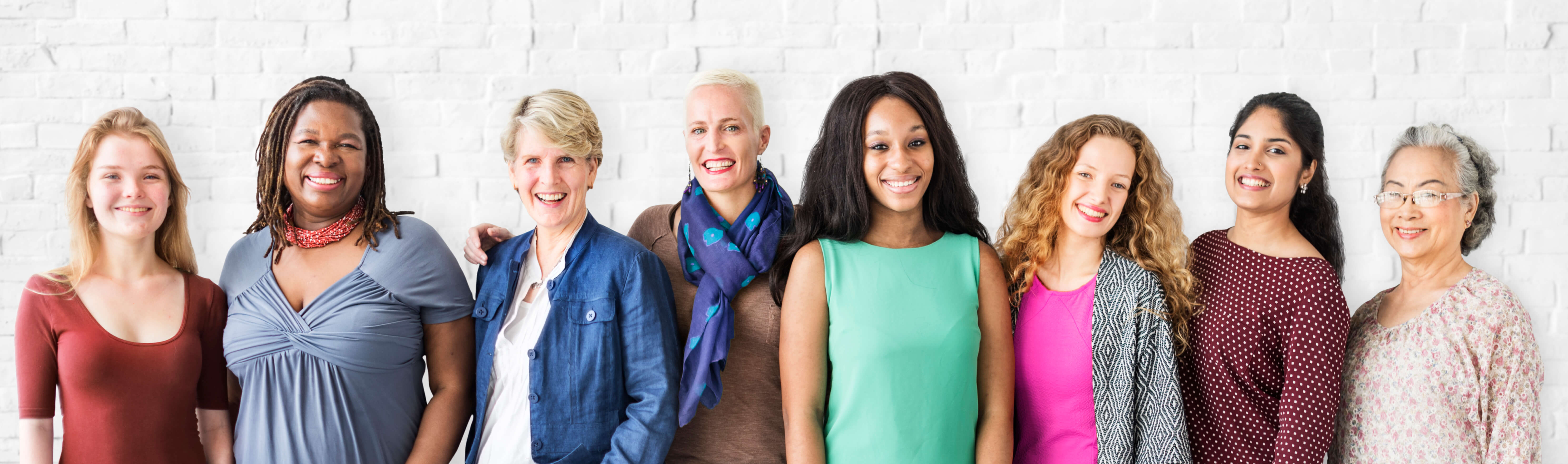 photo of diverse women standing shoulder to shoulder against white brick wall