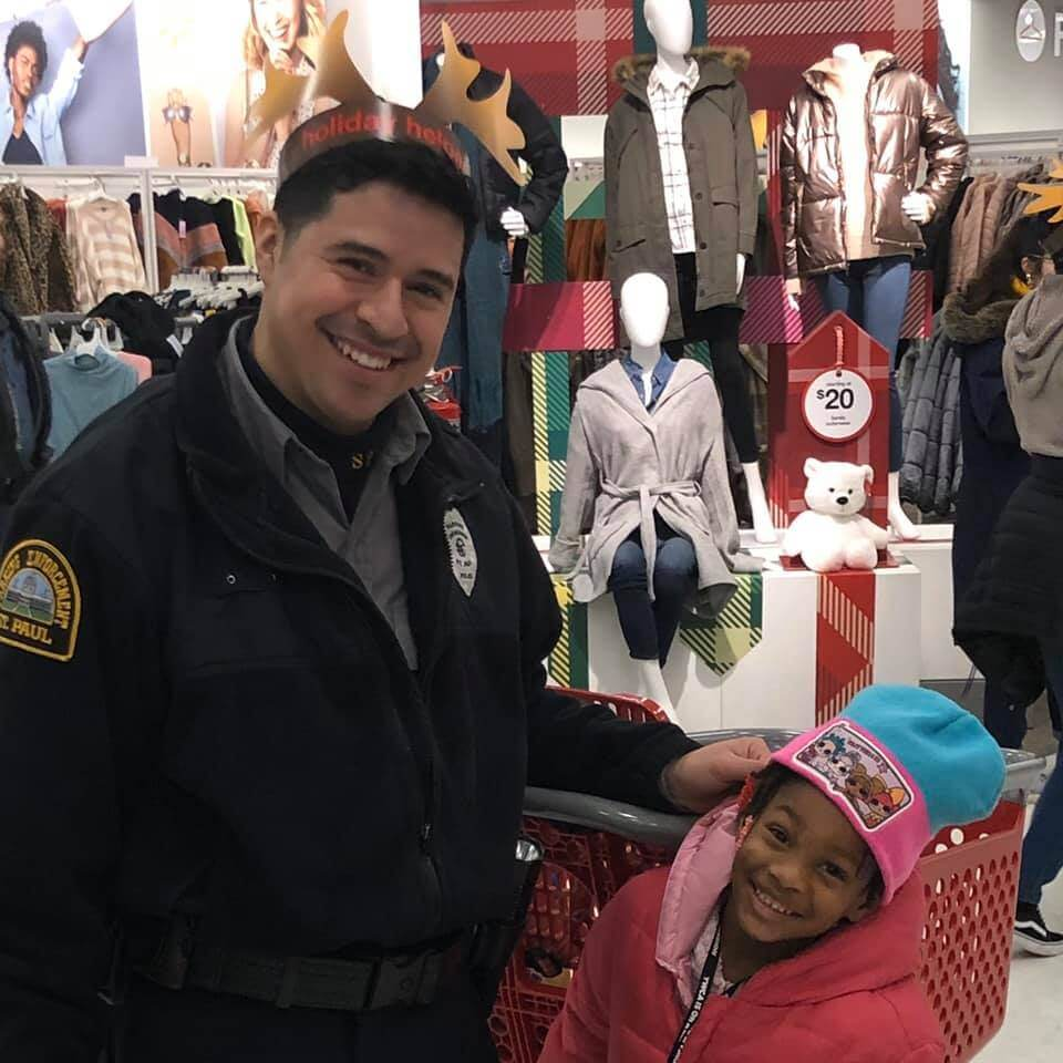 Police officer and young girl shopping at Target, smiling at the camera.