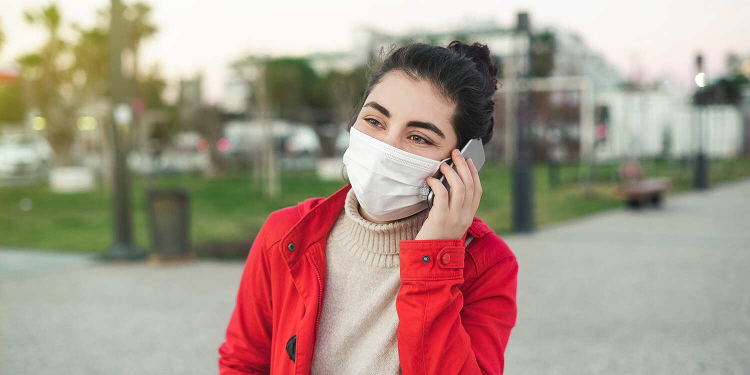 woman talking on the phone with face protective mask