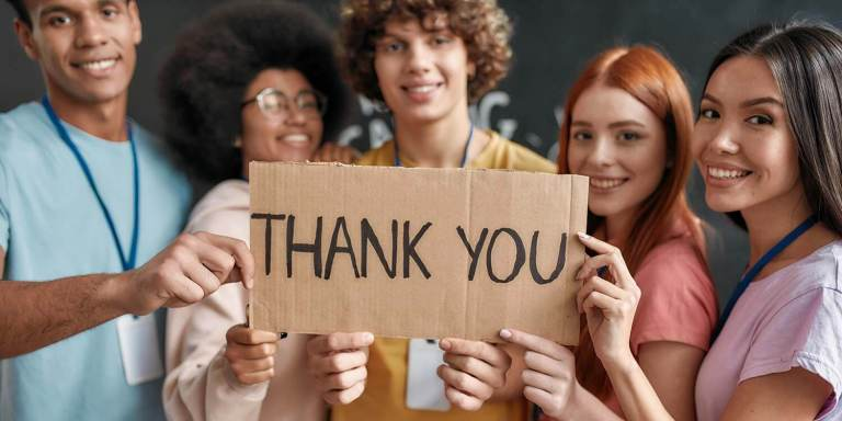Group of diverse young volunteers smiling at camera, holding card with Thank you lettering while standing in charitable organization office