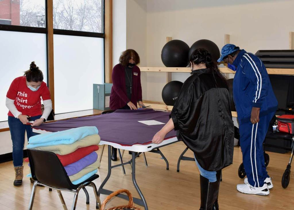 Group of volunteers working on felt blanket
