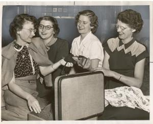 black and white photo of young women unpacking a suitcase