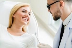 Wurzelbehandlung beim Zahnarzt, Frau lächelt Zahnarzt an