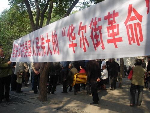 """Una de las pancartas del encuentro: """"Apoyamos firmemente la gran revolución de Wall Street del pueblo estadounidense""""."""