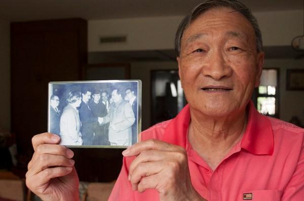 Wang Huaizu en su casa de Pekín. En sus manos, una foto junto a Mao Zedong durante una de las visitas del gobierno cubano a principios de los años 60. [FOTO: Daniel Méndez]