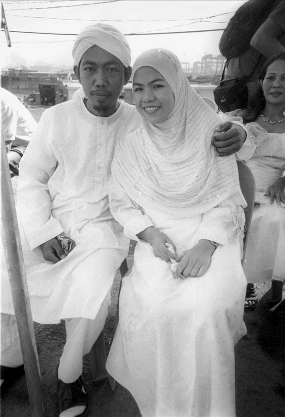 A Muslim couple in the Philippines wait for the start of a mass wedding.